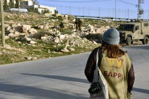 EAPPI-tarkkailija katsoo, kun kolme israelilaista sotilasta on noussut pakettiautostaan tien sivuun.