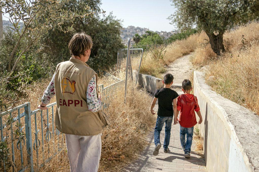 EAPPI-tarkkailija katsoo, kun lapset kävelevät kouluun.
