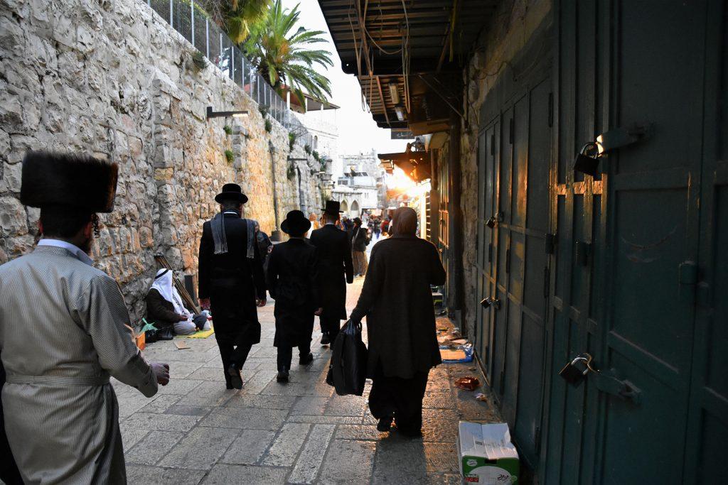 Vanhoillisia juutalaisia miehiä ja musliminainen kävelee vanhan kaupungin katua.
