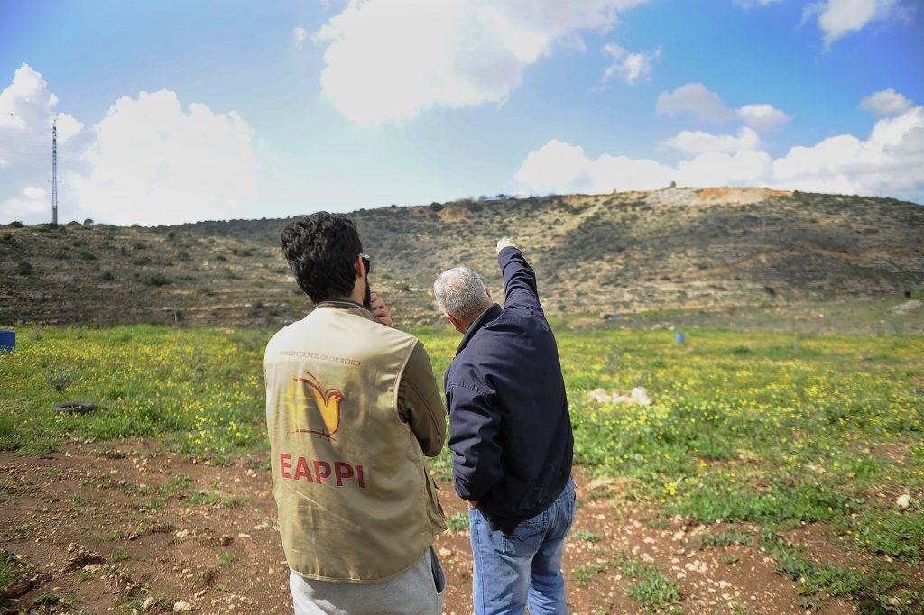 Mies osoittaa EAPPI-tarkkailijalle mäen päällä olevaa rakennusta.