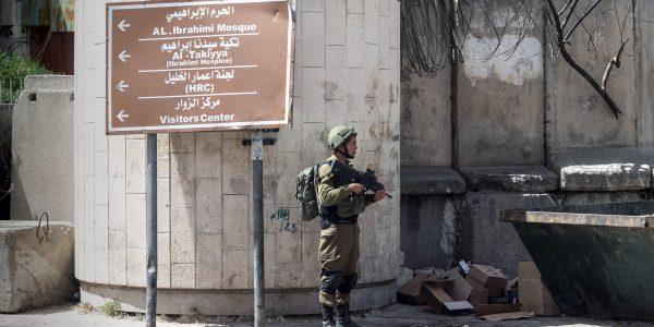 Sotilas seisoo tienviitan ja piikkilangoitetun muurin edessä.