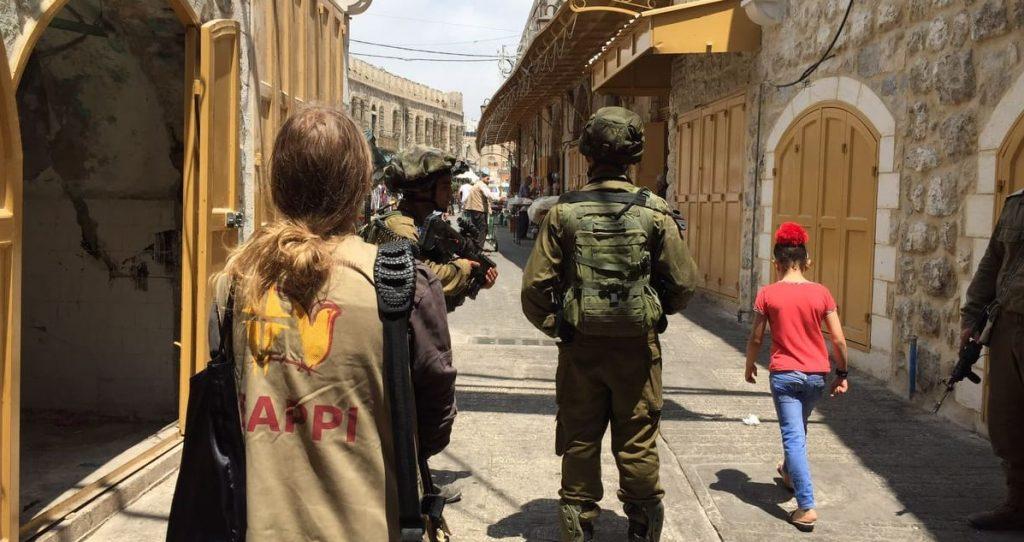 EAPPI-tarkkailija seuraa sotilaita ja lasta Hebronin vanhan kaupungin autiokadulla.