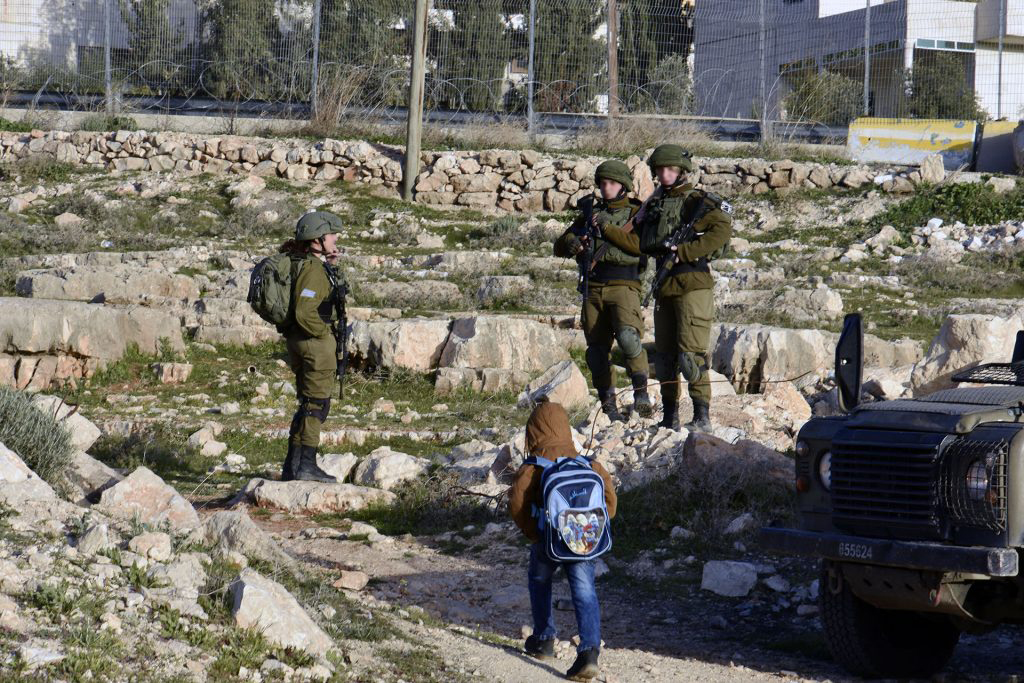 Kolme israelilaista sotilasta tien sivussa ja pieni koululainen reppu selässä.